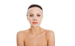 有胶原面具的美丽的妇女在面孔。 免版税库存图片