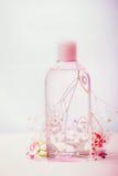 有胶束水或补品的护肤的,桃红色花,淡色,正面图化妆产品瓶 库存图片