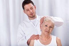 有脖子疼痛的生理治疗师帮助的病人 库存图片