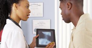 有脖子痛的病人谈话与关于x光芒的医生在片剂 免版税库存照片