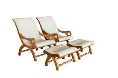 有脚凳的两把白革扶手椅子,隔绝在白色背景 图库摄影