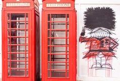 有脚卫兵的街道画的一个电话箱子 库存照片