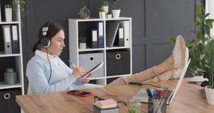 有脚的女实业家在书桌上,当听的音乐和做做名单时 影视素材