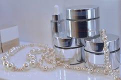 有脸面护理或身体杏仁润肤霜的玻璃开放瓶子在粗麻布 解毒的维生素奶油和珍珠小珠 图库摄影
