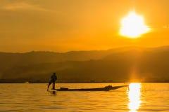 有腿划船的渔夫在日落期间,缅甸的inle湖( 免版税图库摄影