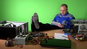 有腿的粗心大意的工程师人在使用与片剂的桌上 股票录像