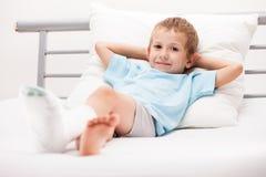 有膏药绷带的小孩男孩在腿脚跟破裂或增殖比 免版税库存图片