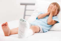 有膏药绷带的小孩男孩在腿脚跟破裂或增殖比 免版税库存照片