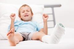 有膏药绷带的小孩男孩在腿脚跟破裂或增殖比 免版税图库摄影