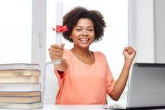 有膝上型计算机、书和文凭的愉快的非洲妇女 库存图片
