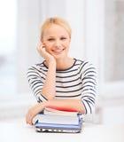 有膝上型计算机、书和笔记本的微笑的学生 库存图片