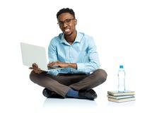 有膝上型计算机、书和bo的愉快的非裔美国人的大学生 免版税库存照片