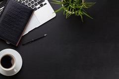 有膝上型计算机、咖啡、笔记薄和植物的办公桌 免版税库存图片