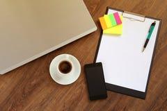 有膝上型计算机、巧妙的电话和咖啡杯的办公室工作场所在木桌上 免版税库存照片