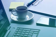 有膝上型计算机、巧妙的电话和咖啡杯的办公室工作场所在桌上 库存图片