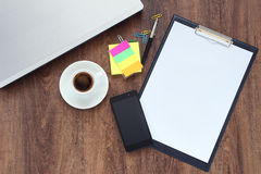 有膝上型计算机、巧妙的电话和咖啡杯的办公室工作场所在桌上 免版税库存照片
