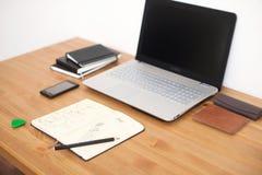 有膝上型计算机、巧妙的电话和笔记本的办公室工作场所在木桌上 库存照片