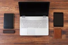 有膝上型计算机、巧妙的电话和笔记本的办公室工作场所在木桌上 图库摄影