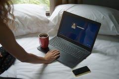 有膝上型计算机、手机和一杯咖啡的妇女在床上的 图库摄影