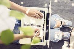 有膝上型计算机、日志和笔的女孩 库存照片