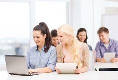 有膝上型计算机、片剂个人计算机和笔记本的学生 免版税库存照片