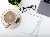 有膝上型计算机、眼睛玻璃、笔记薄、笔和一杯咖啡的书桌在一张白色桌上的 顶视图 平的位置 轻的背景 库存图片