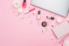 有膝上型计算机、笔记本、化妆用品和花的办公室女性书桌在桃红色背景 顶视图 平的位置概念 库存照片