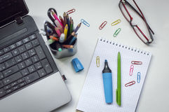 有膝上型计算机、笔记本和标志的书桌 免版税库存照片