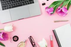 有膝上型计算机、郁金香花、化妆用品、玻璃和笔的办公桌在桃红色背景 平的位置 顶视图 与拷贝空间的概念 图库摄影