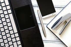 有膝上型计算机、银色笔、智能手机、笔记薄和订书机的现代工作场所在白色木葡萄酒桌上 免版税库存图片