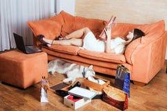 有膝上型计算机、购物袋和多壳的小狗的女性在客厅 库存图片