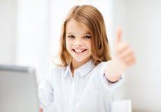 有膝上型计算机个人计算机的女孩在学校 免版税库存照片