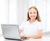 有膝上型计算机个人计算机的女孩在学校 库存照片