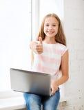 有膝上型计算机个人计算机的女孩在学校 免版税图库摄影