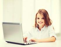 有膝上型计算机个人计算机的女孩在学校 图库摄影