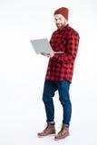 有膝上型计算机个人计算机的英俊的有胡子的人在白色背景 库存照片