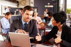 有膝上型计算机会议的两个商人在咖啡店 免版税库存图片