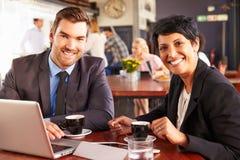 有膝上型计算机会议的两个商人在咖啡店 免版税图库摄影