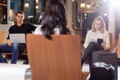 有膝上型计算机和书的乘客在机场等候室 库存照片