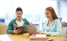 有膝上型计算机和书的愉快的学生在图书馆 免版税库存照片