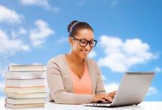 有膝上型计算机和书的非洲学生女孩 免版税图库摄影