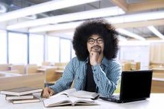 有膝上型计算机和书的非洲学生 免版税库存图片