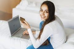 有膝上型计算机和信用卡的一名年轻微笑的妇女 免版税库存图片