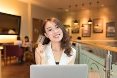 有膝上型计算机和信用卡的亚裔妇女 图库摄影