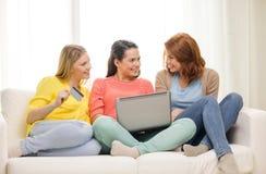 有膝上型计算机和信用卡的微笑的十几岁的女孩 库存图片