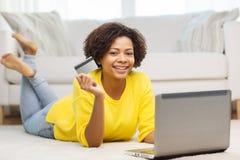 有膝上型计算机和信用卡的愉快的非洲妇女 免版税库存图片