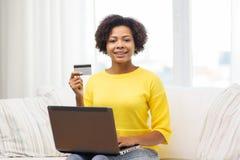有膝上型计算机和信用卡的愉快的非洲妇女 库存图片
