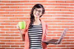 有膝上型计算机和咖啡的亚裔大学生 免版税库存图片