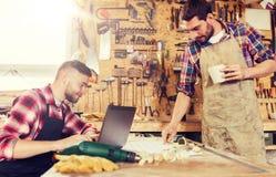 有膝上型计算机和图纸的木匠在车间 免版税图库摄影