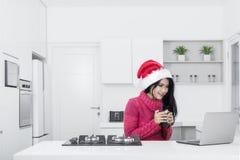 有膝上型计算机和圣诞老人帽子的俏丽的女孩 库存图片